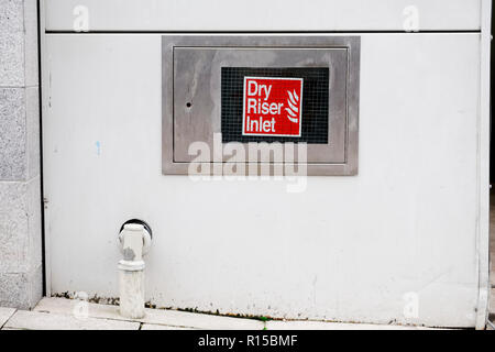 Dry riser inlet box stainless steel on wall office workplace sign - Stock Photo