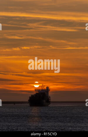 Container vessel leaving the Rotterdam seaport toward the deep ocean under a vivid sunset, Amsterdam, Netherlands - Stock Photo