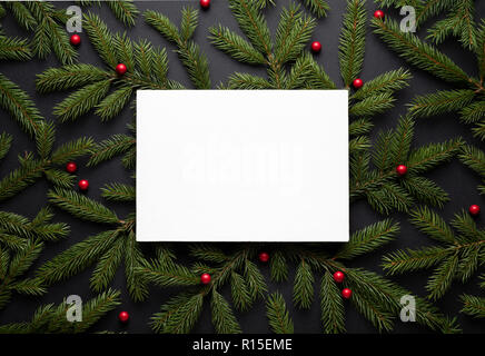 Christmas border. New Year background with copy space for text. Flat lay, top view. Decorative frame of fir branches and holly berries. Paper notice s - Stock Photo