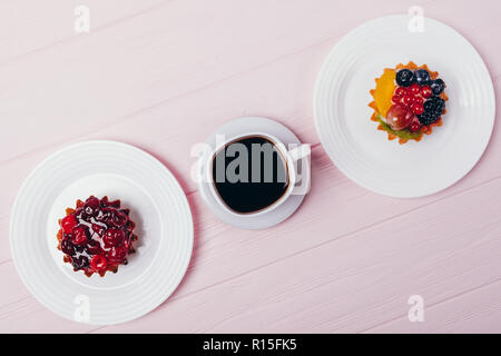 Composition of delicious small cakes with espresso on pink wooden table, top view. Flat lay arrangement of black coffee and berry tartlets. - Stock Photo