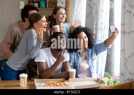 Happy diverse friends make selfie photography on smartphone during lunch. Students eating pizza and drinking coffee together indoors. Leisure activiti - Stock Photo