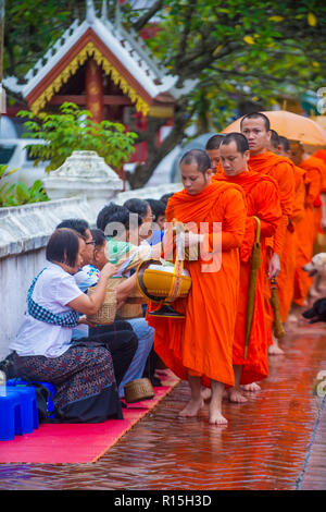 LUANG PRABANG , LAOS - AUG 11 2018 : Buddhist alms giving ceremony in Luang Prabang Laos on August 11 2018. It is estimated that about 1 in 3 male Lao - Stock Photo