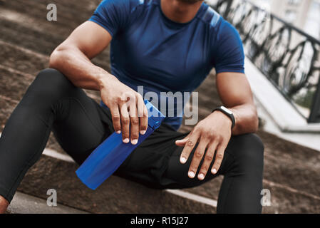 Attractive sportsman with fitness thracker holding mobile phone while sitting on steps with water bottle outdoors. Cropped photo - Stock Photo