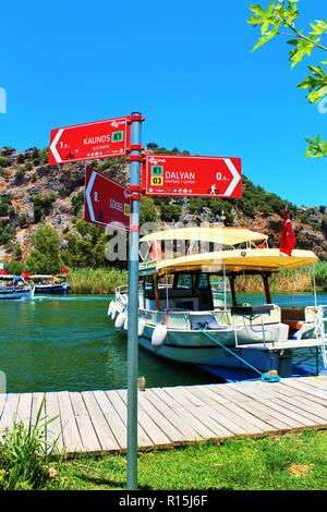 Dalyan, Turkey - July 7th 2018: A signpost pointing to the Kaunos ruins and Dalyan town, by the river Cayi, popular with passenger boats. - Stock Photo