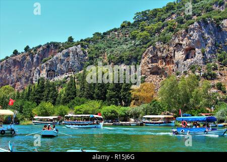 Dalyan, Turkey - July 7th 2018: The Lycian Tombs landmark above the Cayi river, filled with boats and tourists. - Stock Photo