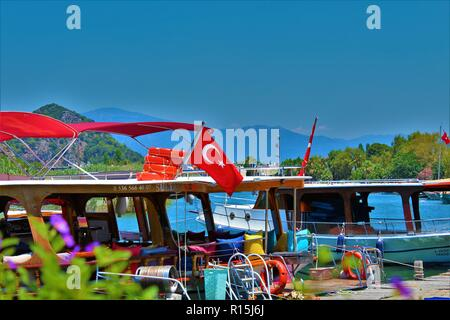Dalyan, Turkey - July 7th 2018: Passenger boats moored on the river Cayi with a view  of the mountains in the background. - Stock Photo