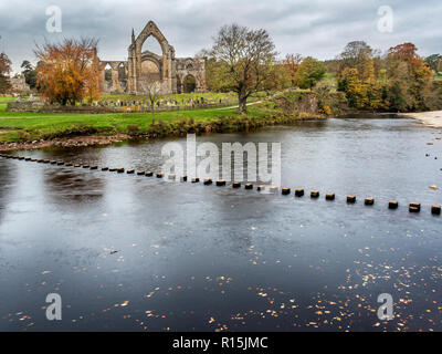 Stepping stones across the River Wharfe and the ruins of Bolton Priory in autumn Bolton Abbey Yorkshire Dales England - Stock Photo