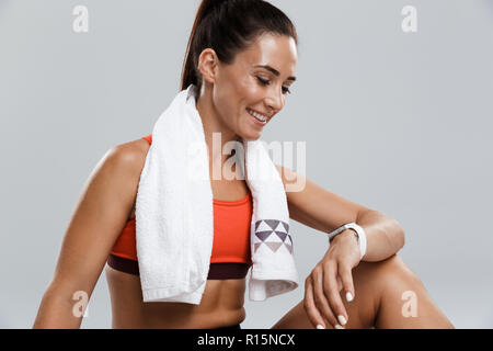 Image of a beautiful strong happy cheerful young sports woman posing isolated indoors with towel looking at watch. - Stock Photo