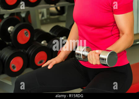 Young woman trains biceps in modern gym - Stock Photo