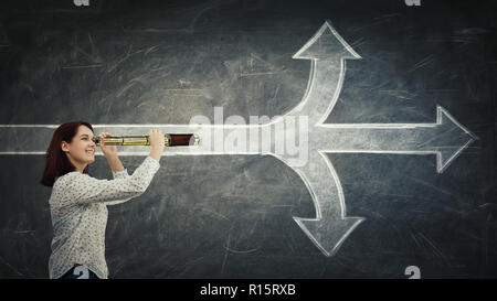Positive, young woman looking through a spyglass in front of a blackboard as a crossroad arrows splitted in three different ways. Choosing between up, - Stock Photo
