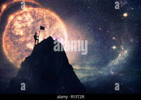Self overcome concept as a man leader climbing a tall mountain carrying a flag to the top. Road to win and success over starry night sky cosmic backgr - Stock Photo