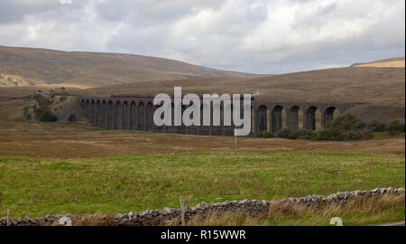 A steam train crosses the historic Ribblehead Viaduct in the heart of the Yorkshire Dales National park - Stock Photo