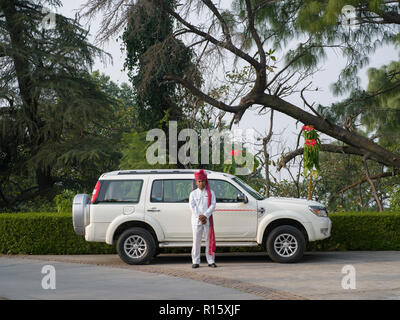 Chauffer standing in front of luxury vehicle, AnandaIn the Himalayas, Narendranagar, Tehri Garhwal, Uttarakhand, India - Stock Photo