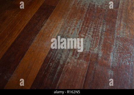 Old scratched hardwood flooring in need of maintenance. parquet ruined by scratches made by prolonged use of chair. - Stock Photo