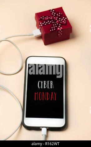 closeup of a smartphone with the text happy cyber monday in its screen, connected to a gift by a cable, placed on an off-white surface - Stock Photo