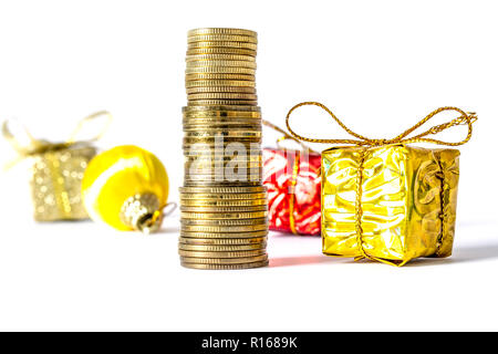 Gift in a gold box with a bow next to gold coins column on a background of other gifts isolated on a white background - Stock Photo