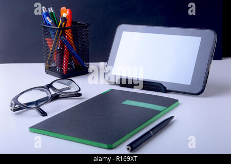 Modern white office desk table with laptop, smartphone and other supplies. Blank notebook page for input the text in the middle. Top view. - Stock Photo