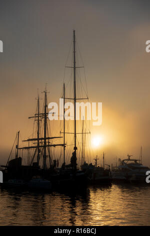 Ships silhouetted against dawn sky in Poole - Stock Photo
