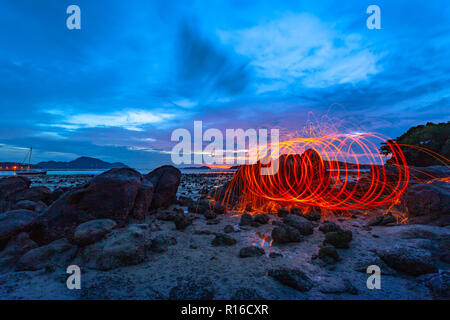 light lines of steel wool with long exposure speed motion abstract at sunrise on the rock - Stock Photo