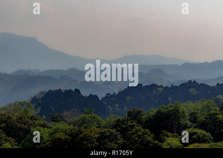 Thakhek, Laos - April 21 2018: Stunning limestone hills surrounded by green in the Khammouane province in Laos - Stock Photo