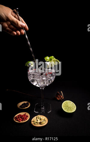 barman preparing a tasty and fresh gin and tonic cocktail on a black background next to his ingredients - Stock Photo