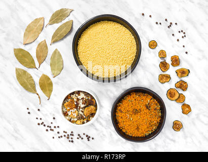 Couscous, risotto and cooking ingredients on marble background. Laurel leaves, dried zucchini and black pepper. - Stock Photo