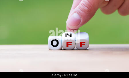 Hand turns a dice and changes the word 'off' to 'on' - Stock Photo