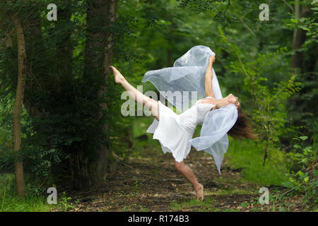 Mystical portrait of a beautiful graceful barefoot woman in a fresh white dress with her arms draped in filmy sheer fabric posing with one leg raised  - Stock Photo