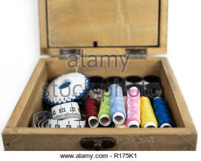 Small old wooden box with color threads, measuring tape and other sewing equipment, viewed in closeup and isolated on white background - Stock Photo