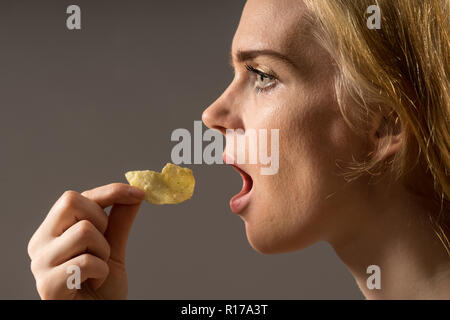 Junk food and unhealthy eating concept. Portrait of young woman who holding fried potato chips at the mouth, posing over gray background. Studio shot - Stock Photo