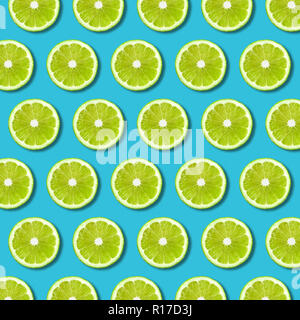 Green lime slices pattern on vibrant turquoise color background. Minimal flat lay food texture - Stock Photo