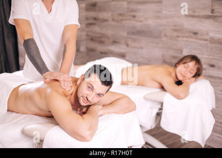 body treatment . massage therapist giving massage to young couple - Stock Photo