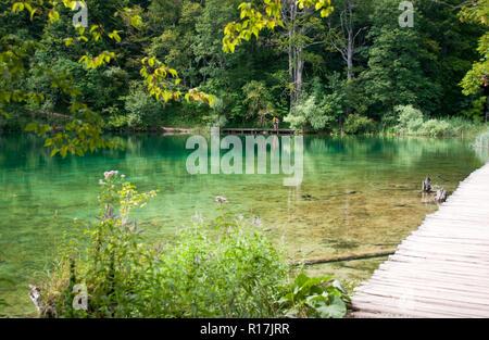 Tourists walking along a hiking path across the lake - Stock Photo