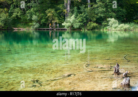 Small figures of tourists walking along a hiking path across the lake with emerald transparent water. Plitvice lakes national park, Croatia - Stock Photo