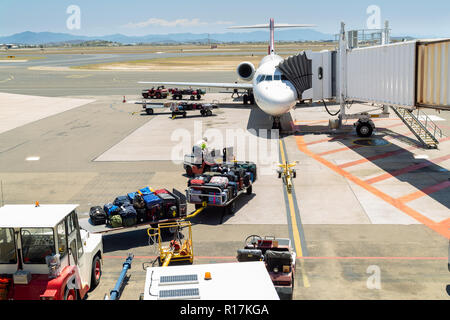 Crew preparing to load luggage onto plane in preparation for takeoff at Townsville airport, North Queensland, Australia - Stock Photo