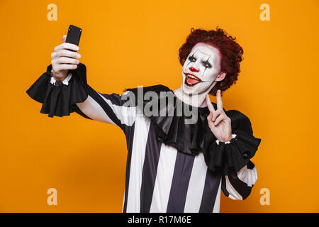 Smiling scary man clown with red hair and scary make-up making selfie on smartphone isolated over orange - Stock Photo