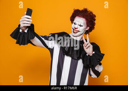 Joyful clown man 20s wearing black costume and halloween makeup taking selfie photo on mobile phone isolated over yellow background - Stock Photo