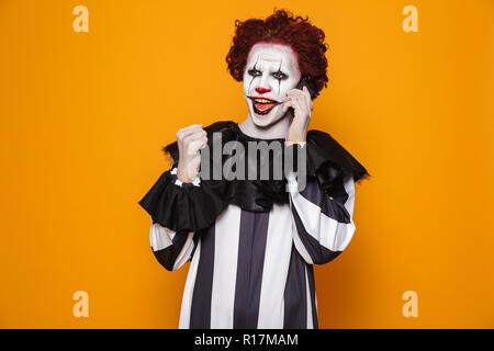 Joyful clown man 20s wearing black costume and halloween makeup talking on smartphone isolated over yellow background - Stock Photo