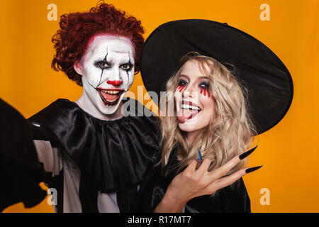 Photo of joyful witch woman and clown man wearing black costume and halloween makeup taking selfie isolated over yellow background - Stock Photo