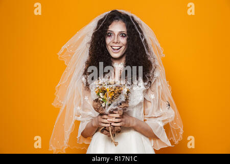 Smiling dead bride in wedding dress and veil holding flowers and smiling to camera isolated ove orange - Stock Photo
