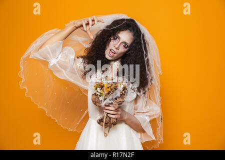Creepy dead bride in white wedding dress looking camera and scary isolated over orange - Stock Photo