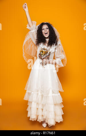 Happy bride zombie in wedding dress and veil screaming and laughing isolated over orange - Stock Photo