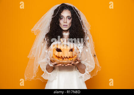 Creepy dead bride in wedding dress and veil looking camera and holding pumpkin isolated over orange - Stock Photo