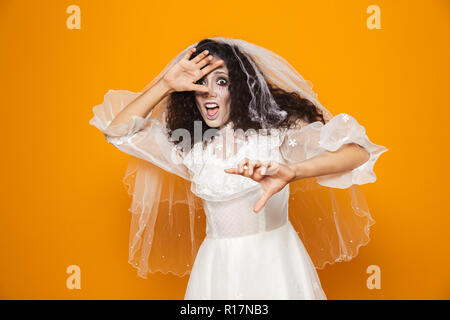 Frightened woman zombie in wedding dress and viel looking camera and hiding with hands isolated over orange - Stock Photo