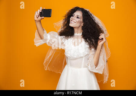 Cheerful bride zombie in wedding dress and veil making selfie on smartphone isolated over orange - Stock Photo