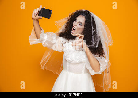 Scary creepy bride with halloween make-up in wedding dress making selfie isolated over orange - Stock Photo