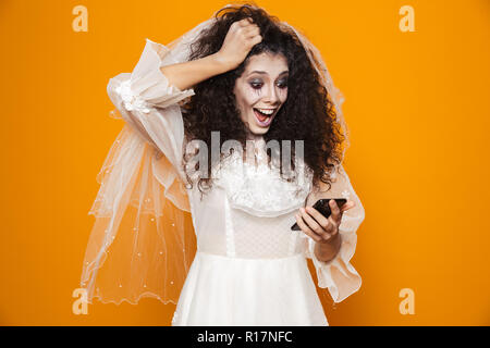 Surprised happy bride zombie in wedding dress using smartphone and smiling isolated over orange - Stock Photo