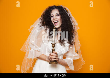 Cheerul beautiful dead bride in wedding dress holding candle and looking camera isolated over orange - Stock Photo