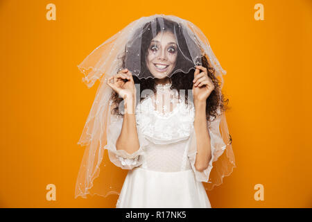 Happy dead bride in wedding dress put on veil and smiling to camera isolated over orange - Stock Photo