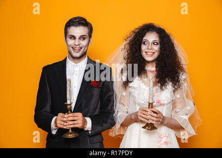 Happy couple dressed in scary Haloween costumes standing isolated over yellow background - Stock Photo